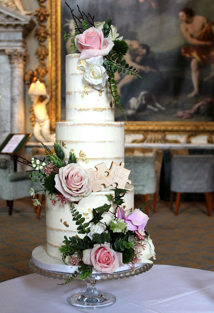 Semi Naked Wedding Cake with Heavy Foliage & Pastel Flowers