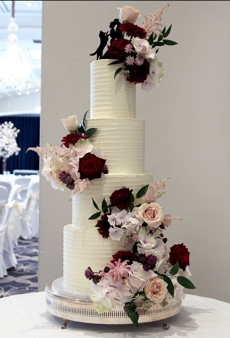 White Ripple Wedding Cake with Deep & Pale Heavy Flowing Flowers