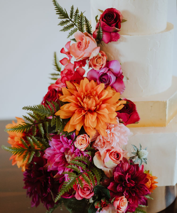 Hexagon Wedding Cake with a Gold Tier & Bright Flowers Details