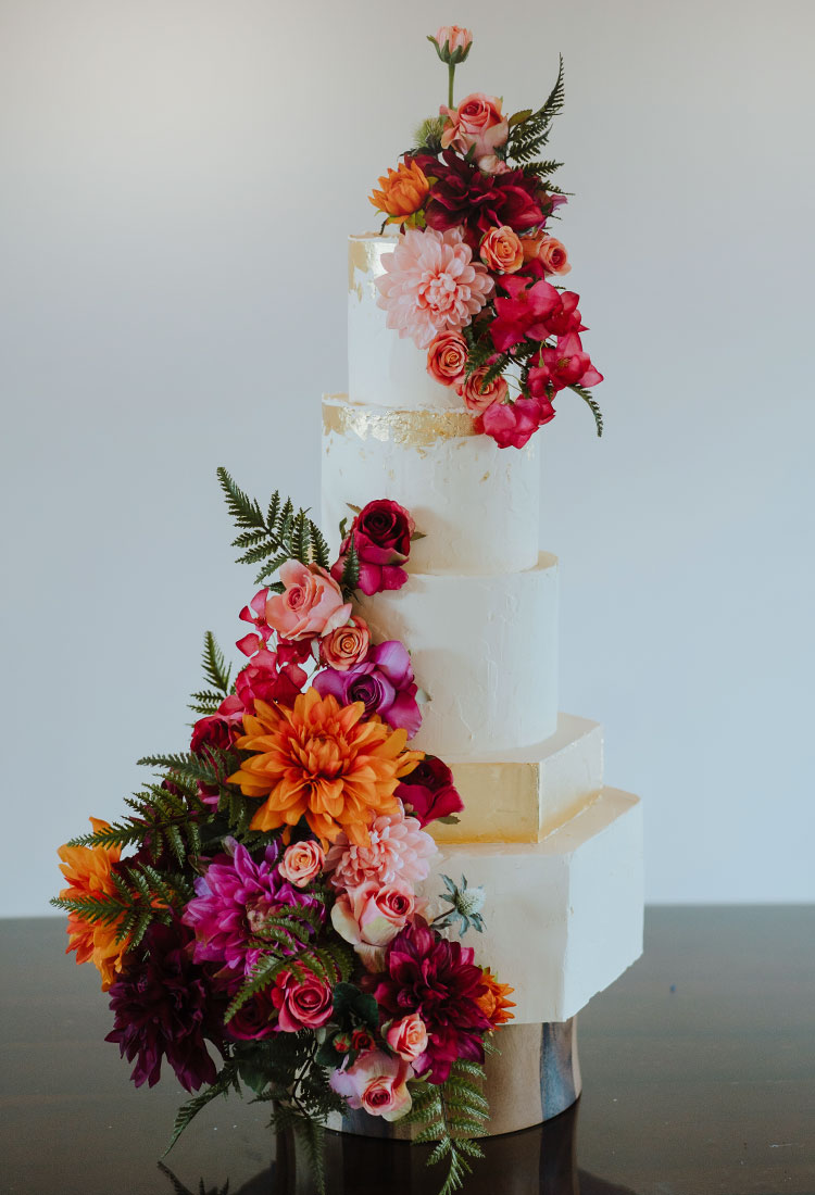 Hexagon Wedding Cake with a Gold Tier & Bright Flowers